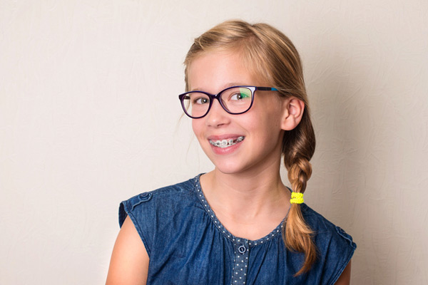 Young blonde girl with glasses smiling with her braces